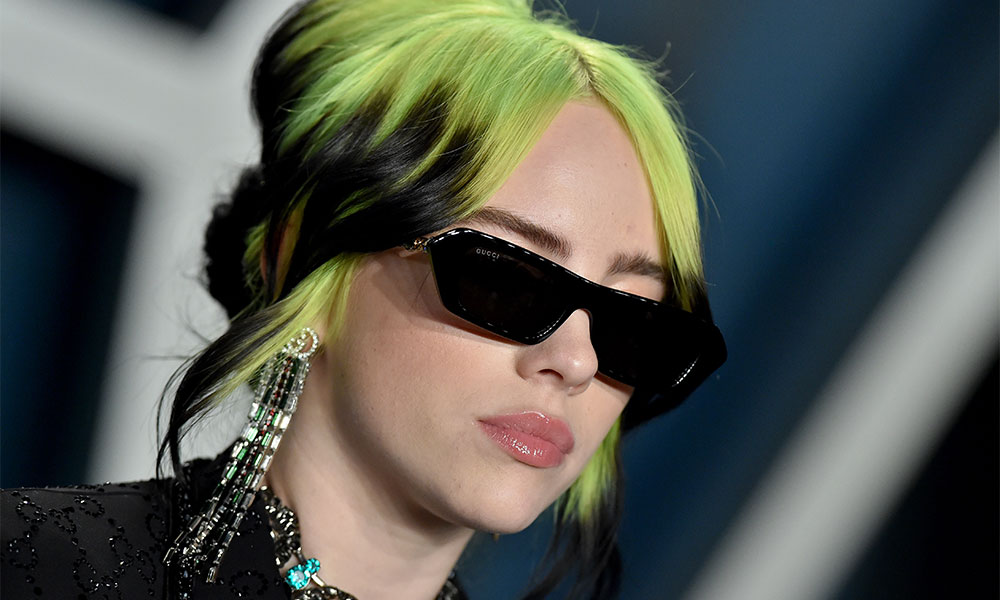 Billie Eilish with green hair and sunglasses