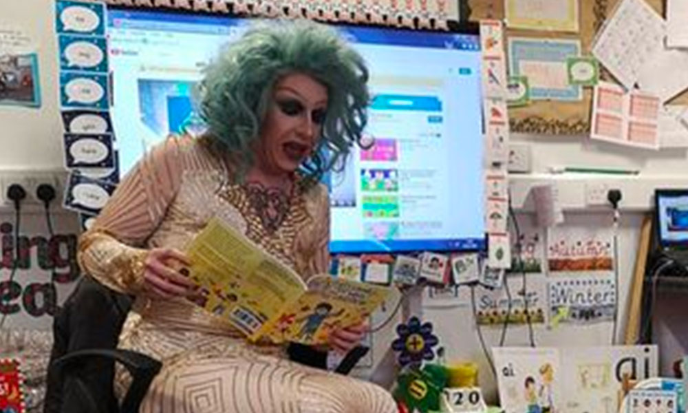 Drag queen story time performer Flowjob reading a book in a classroom