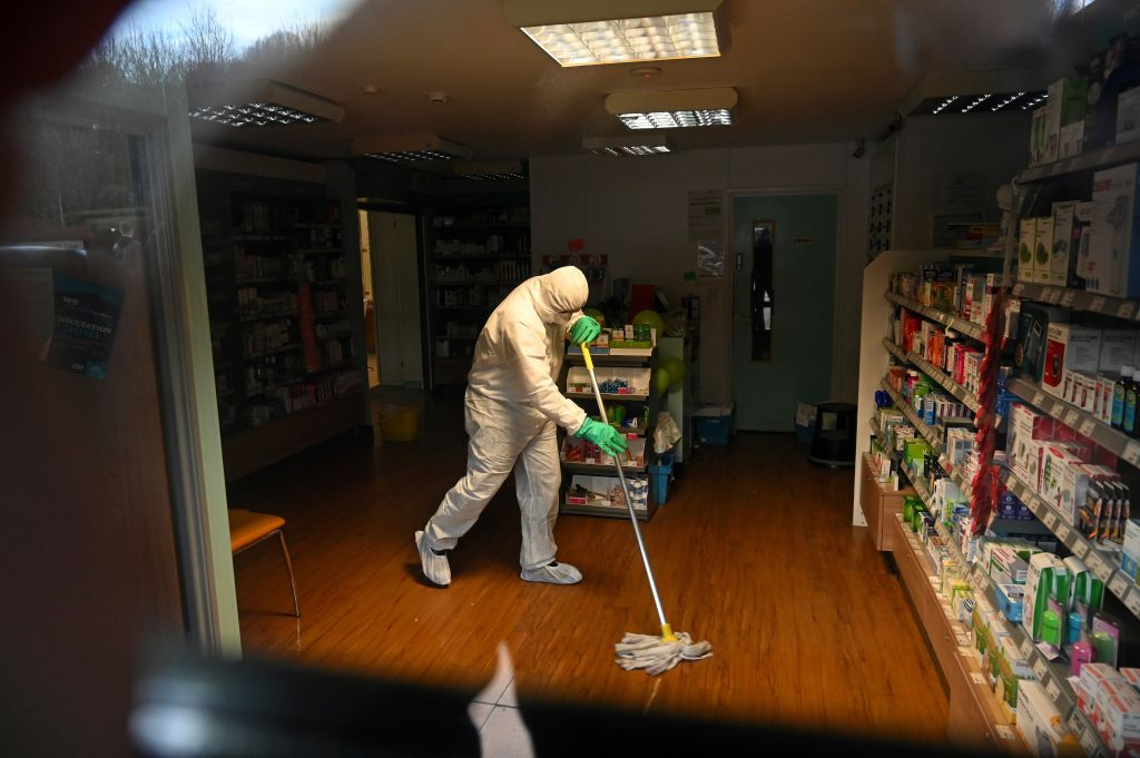 A worker in protective clothing, including face mask and gloves, is pictured cleaning the floor of a pharmacy