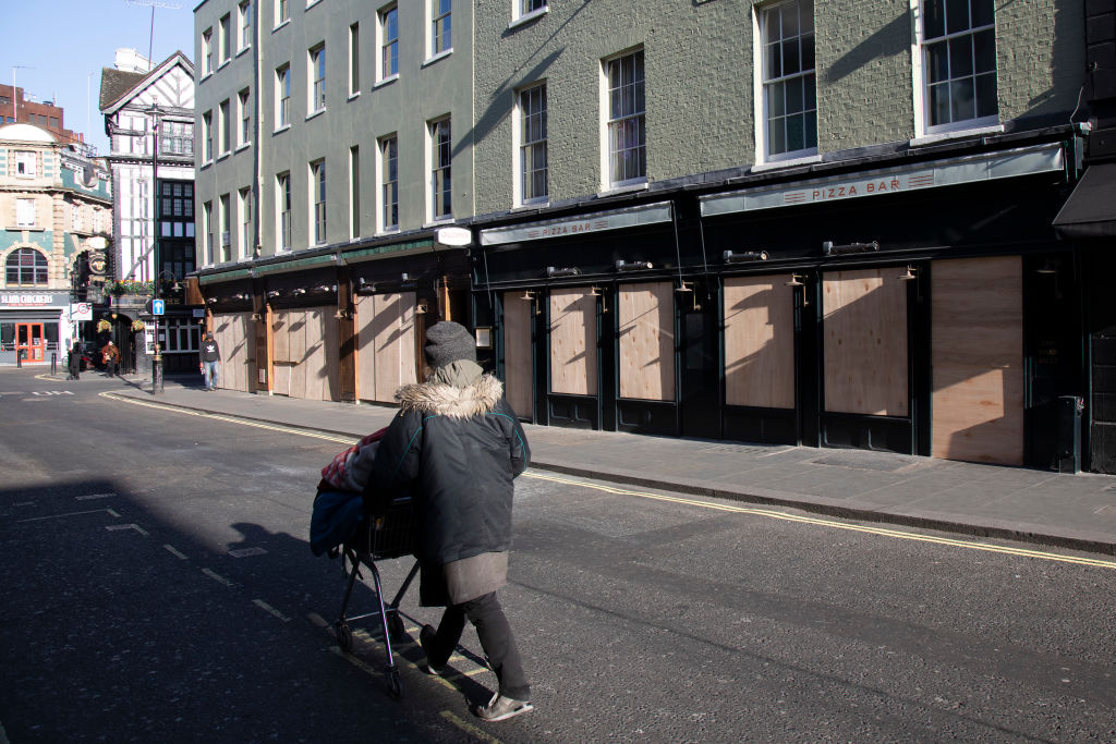 Bars and restaurants boarded up and closed down on Old Compton Street in Soho, at the heart of the West End