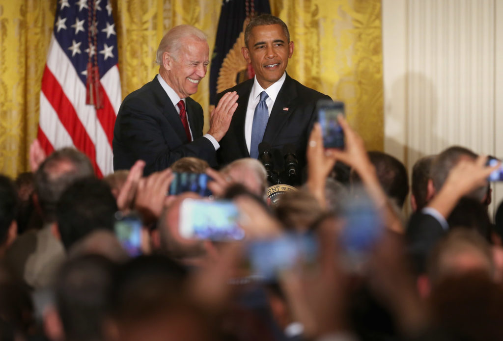 Former US president Barack Obama (R) and vice president Joe Biden react after a heckler is removed from a reception for LGBT Pride Month in the East Room of the White House. (Chip Somodevilla/Getty Images)