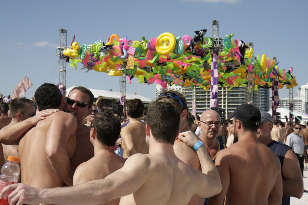 A group of men hugging at the Winter Party Festival on Miami Beach. At least one attendee in 2020 acquired the coronavirus, according to organisers. (Jeffrey Greenberg/Universal Images Group via Getty Images)