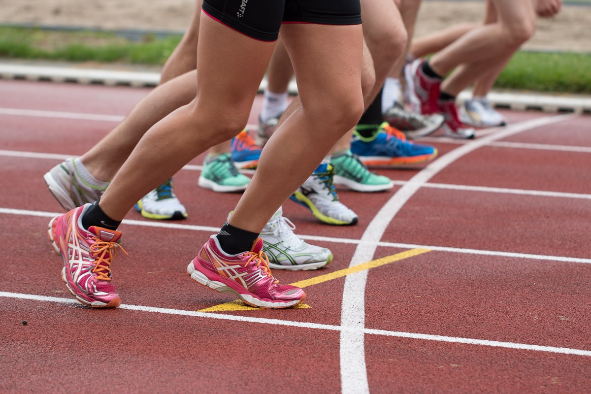 Women line up to sprint on a running track