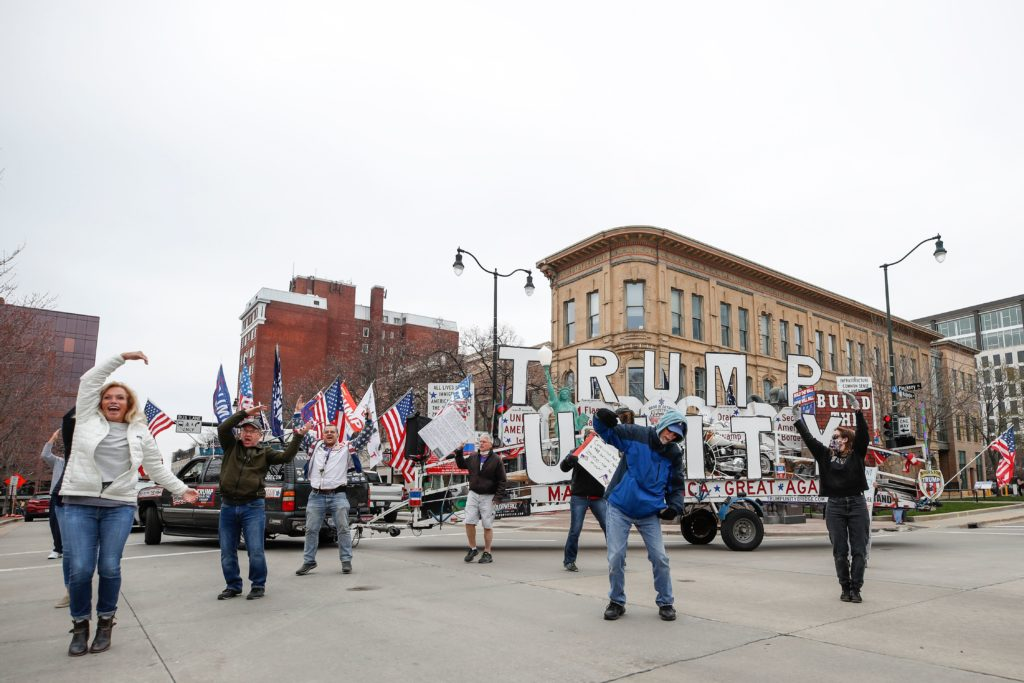 People hold signs during a protest against the coronavirus shutdown in front of State Capitol in Madison, Wisconsin, on April 24 2020. (KAMIL KRZACZYNSKI/AFP via Getty Images)