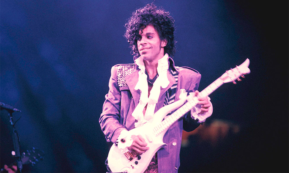 Prince performing on stage during his Purple Rain tour.