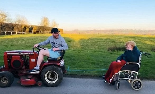 Tommy Ferris tows his grandmother's wheelchair on his sit-down lawnmower. (Screen capture via BBC)