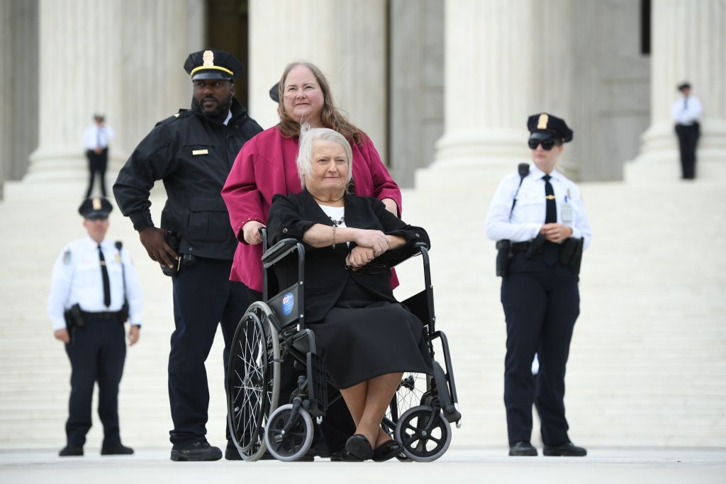 Transgender activist Aimee Stephens,with her wife behind, sits in her wheelchair outside the US Supreme Court in Washington, DC, October 8, 2019