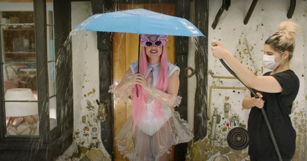 Lady Gaga holding an umbrella as her assistant pours water from a hose on her, or a work of art? (Screen capture via YouTube)