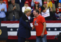 US president Donald Trump shakes hands with Minneapolis Police Union head Bob Kroll on stage during a campaign rally at the Target Center on October 10, 2019 in Minneapolis, Minnesota