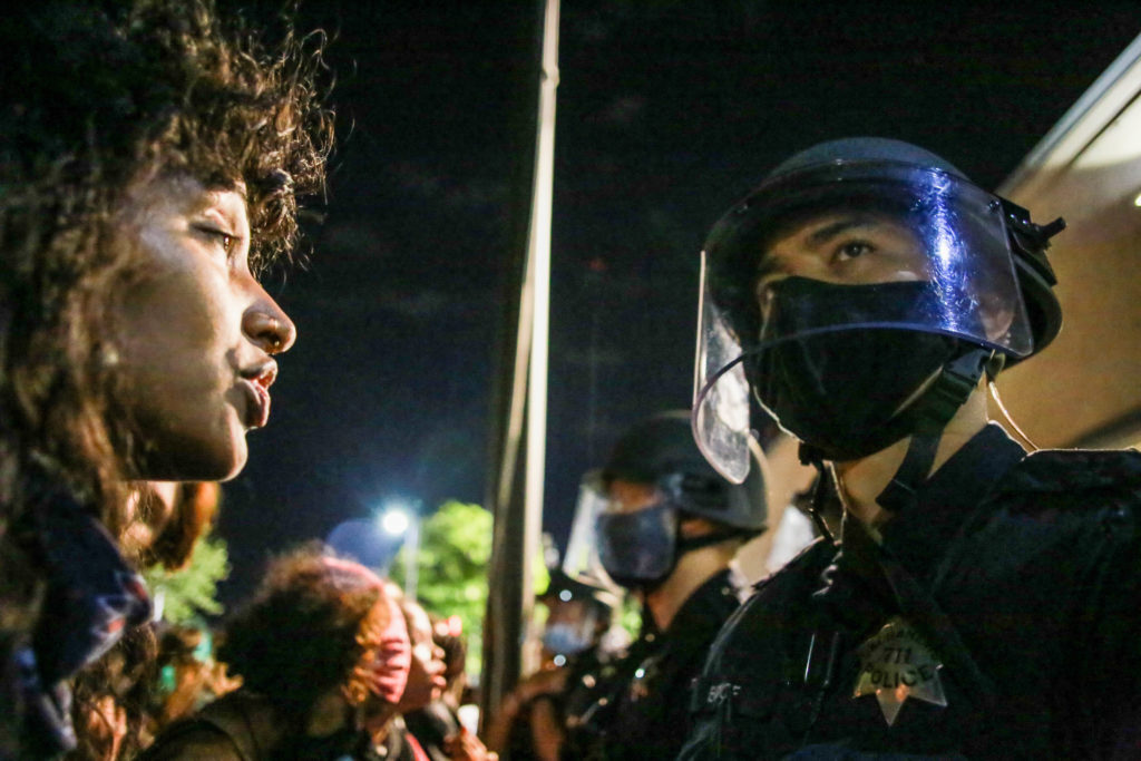 A protester stands face to face with a police officer during a peaceful Black Lives Matter demonstration in 2020. (Stanton Sharpe/SOPA Images/LightRocket via Getty Images)