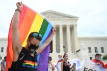 A man waves a rainbow flag in front of the Supreme Court.