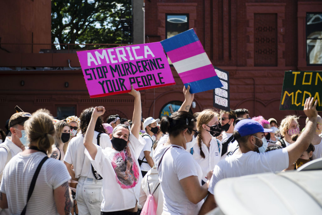 Protestors march with chants, trans Pride flags, signs and white clothing in support of Black Trans Lives Matter on June 14, 2020. (Michael Noble Jr./Getty Images)