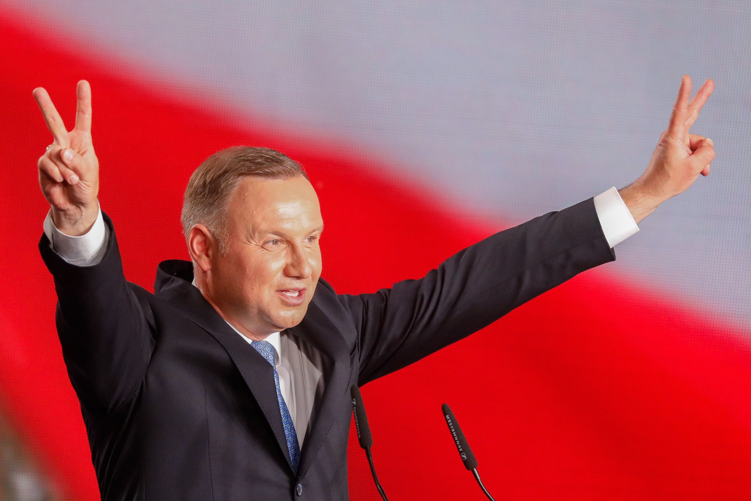 Polish President Andrzej Duda flashes V-signs after addressing supporters as exit poll results were announced during the presidential election in Lowicz, Poland