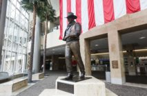 A statue of John Wayne is on display beneath an American flag in John Wayne Airport, located in Orange County, on June 28, 2020 in Santa Ana, California. Orange County