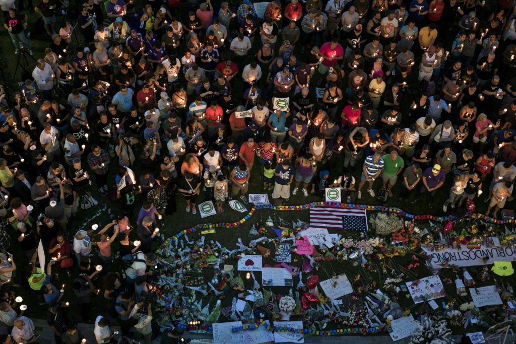 Mourners hold candles while observing a moment of silence during a vigil outside the Dr. Phillips Center for the Performing Arts for the mass shooting victims at the Pulse nightclub June 13, 2016. (BRENDAN SMIALOWSKI/AFP via Getty Images)