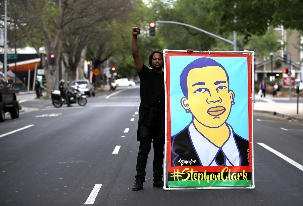 A Black Lives Matter protester holds an illustration of Stephon Clark during a march on April 4, 2018 in Sacramento, California. (Justin Sullivan/Getty Images)