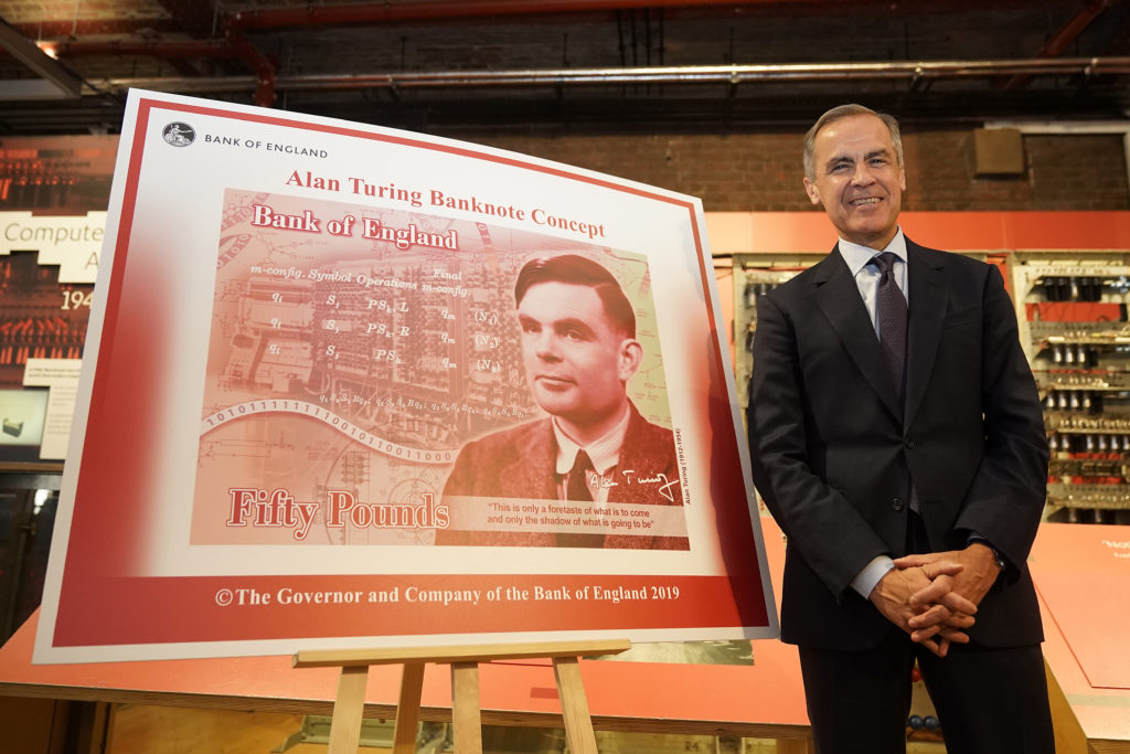 Mark Carney in front of a large illustration of the Alan Turing note