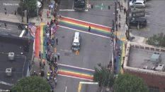 The casket of John Lewis, a towering giant in the civil rights movement, pauses as crowds cheer at a Pride flag-inspired crossroads in Atlanta, US. (Screen capture via Facebook)