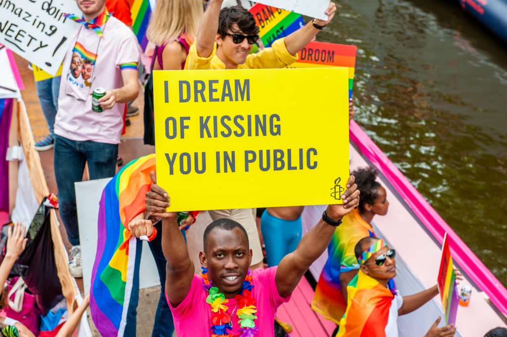 A black man holds a placard on the boat of Amnesty International during Amsterdam's famous canal pride parade