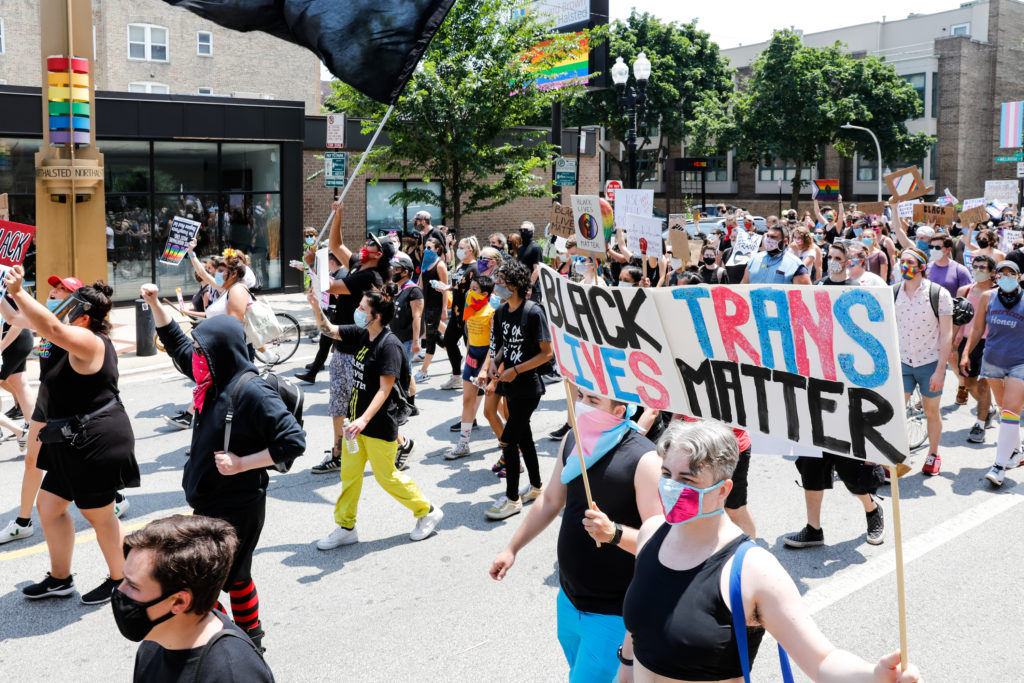 Protesters hold signs during the Pride Without Prejudice march in Boystown on June 28, 2020 in Chicago, Illinois. (Natasha Moustache/Getty Images)