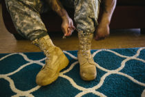 Army Sergeant Shane Ortega laces up boots before posing for a portrait at home at Wheeler Army Airfield on March 26, 2015 in Wahiawa, Hawaii.