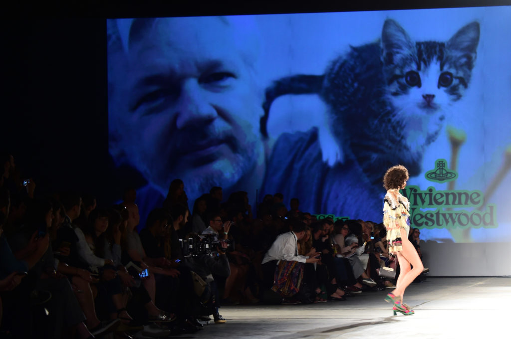 A picture of WikiLeaks founder Julian Assange is seen on a giant screen at the show for fashion house Vivienne Westwood during the Men's Spring/Summer 2017 fashion show. (GIUSEPPE CACACE/AFP via Getty Images)