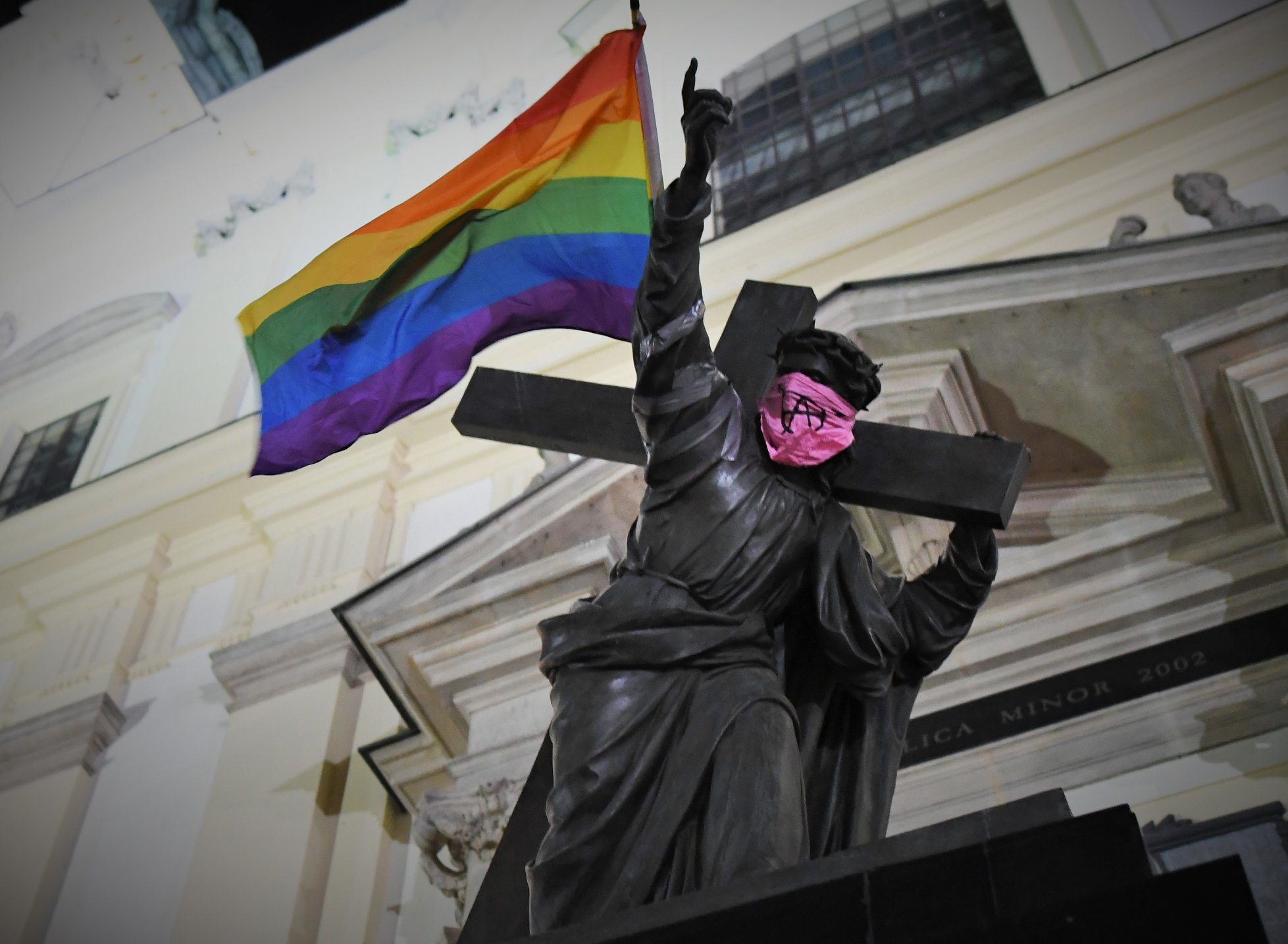 Statue of Jesus carrying Pride flag and wearing anarchist bandana