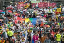 People hold placards and rainbow flags during a Pride event in Czech capital Prague on August 10, 2019