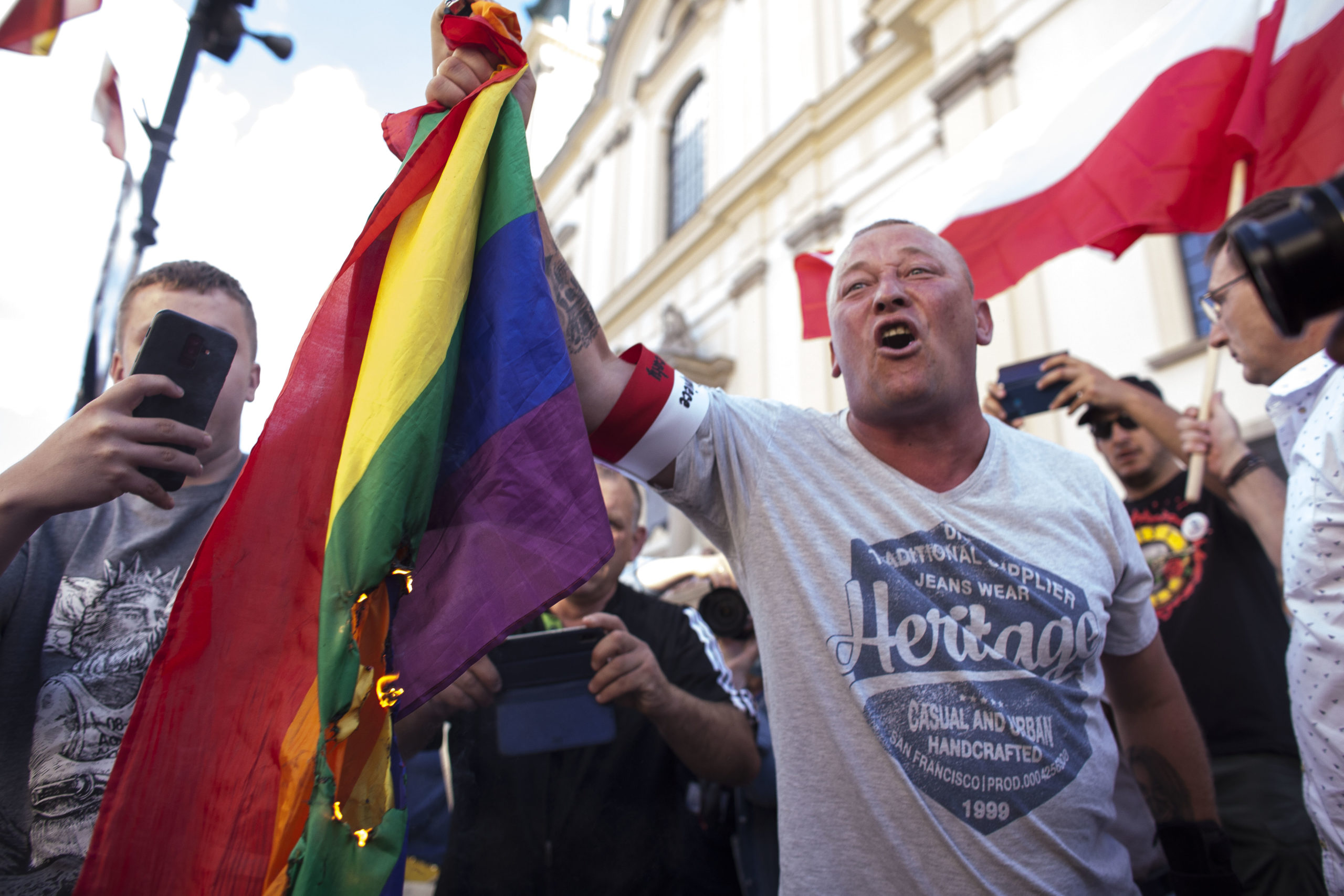 A man burns a LGBT flag during the anniversary of Warsaw Uprising in Warsaw, Poland