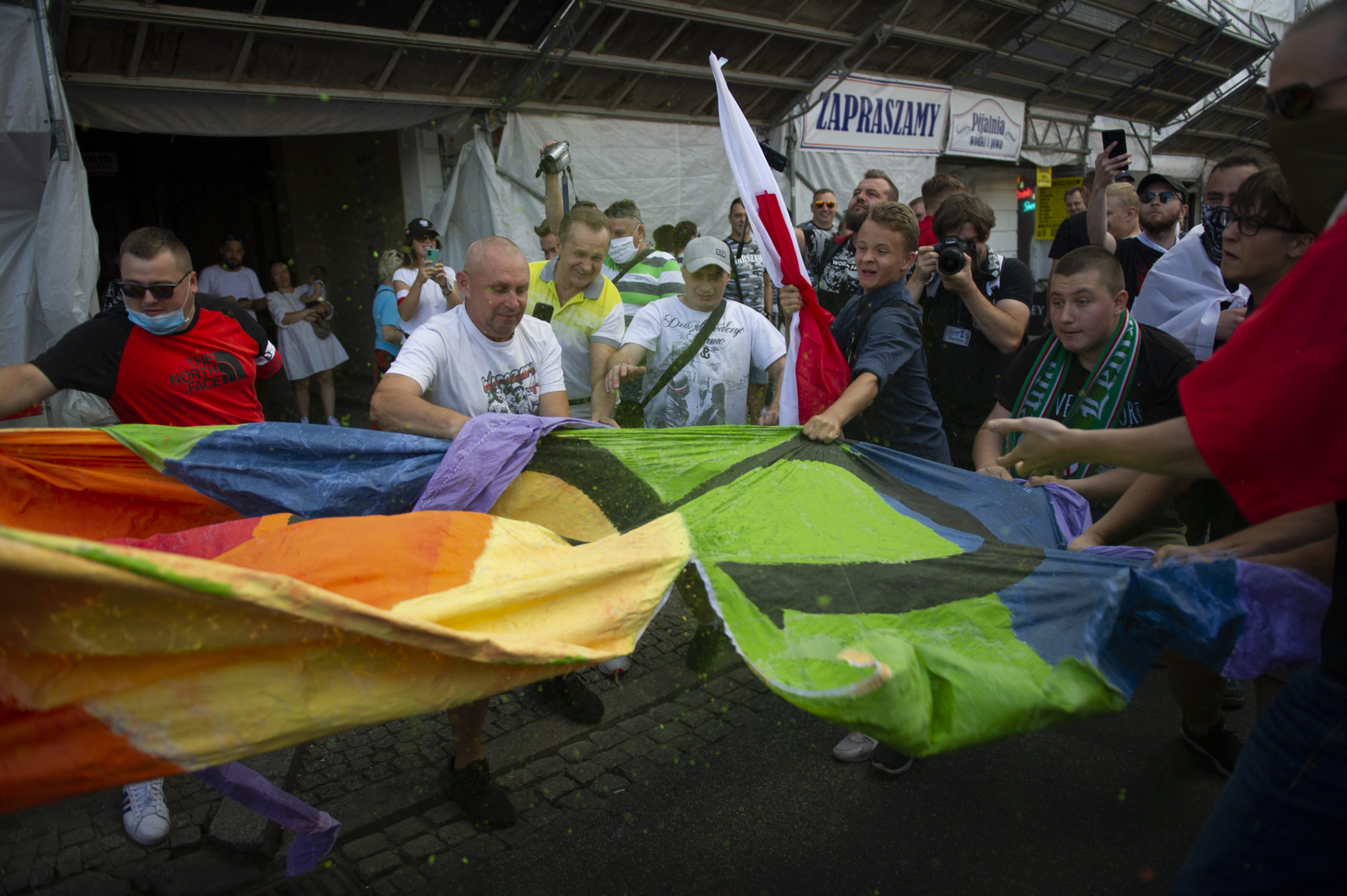 Demonstrators tear a rainbow flag apart during the 76th Warsaw uprising anniversary