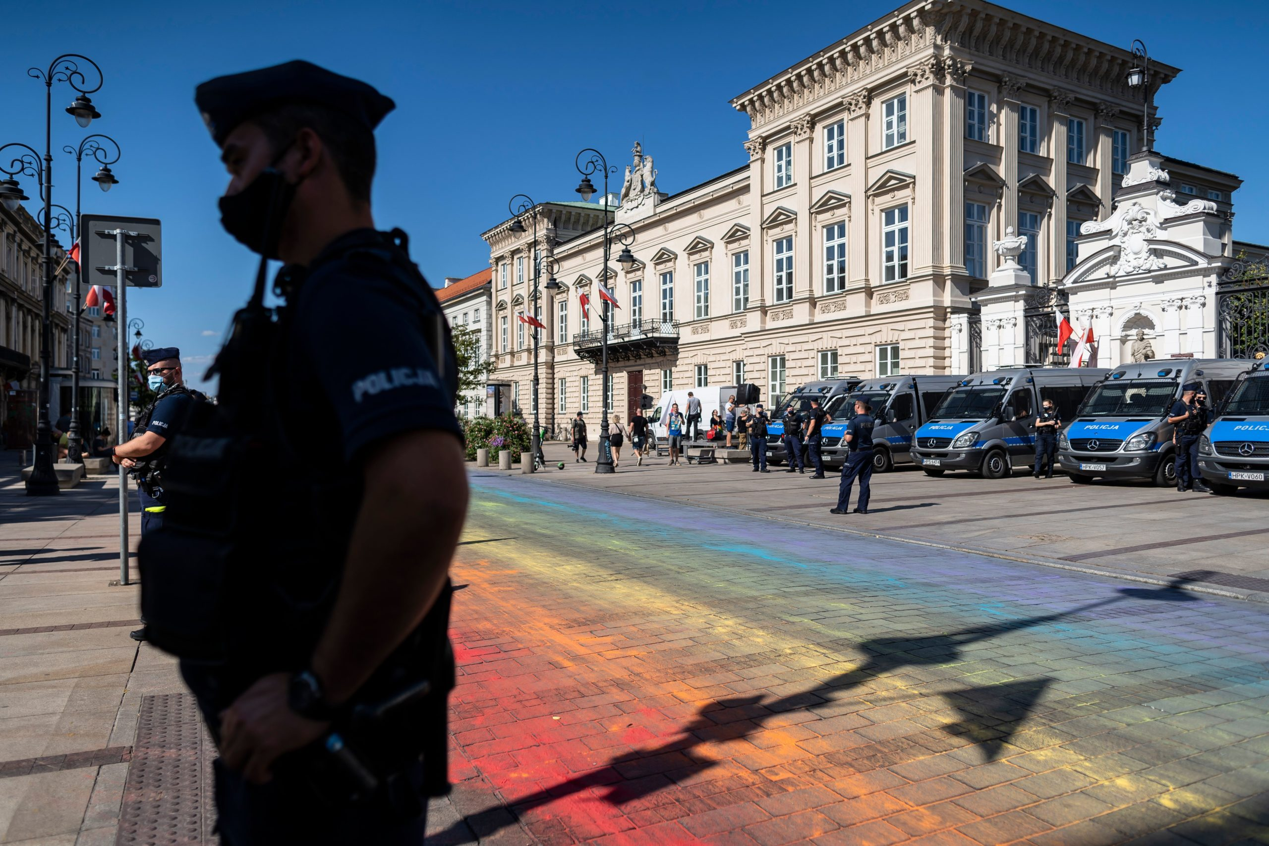 Police stand guard after the street is painted in rainbow colours