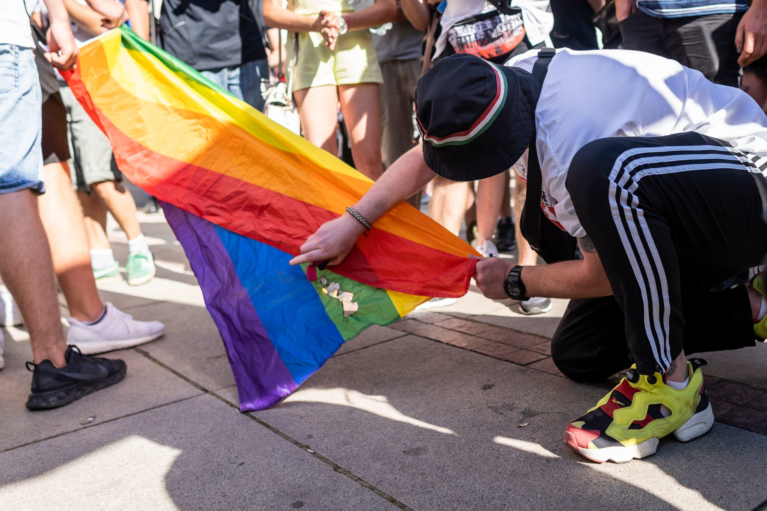An activist attempts to burn a rainbow flag in front of the Warsaw University