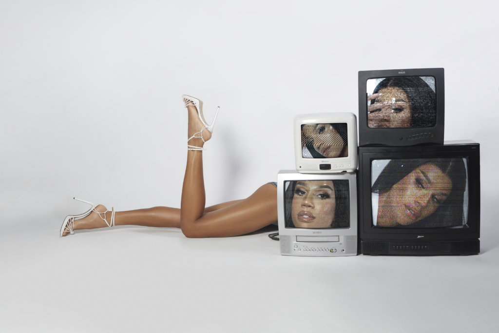 Naomi Smalls lying down behind a stack of old televisions, her legs are all that's visible. Each screen has a close-up of her face