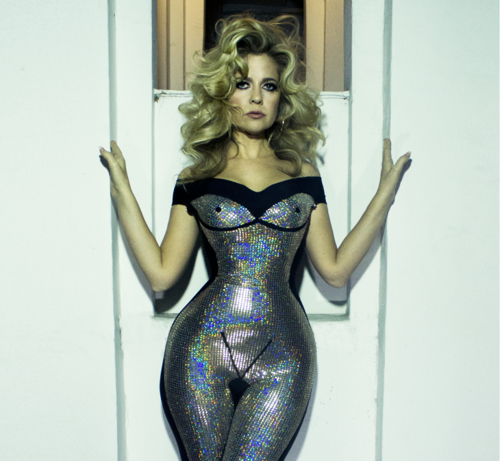 Charlotte Awbery in a silver jumpsuit with line drawings of boobs and a vulva