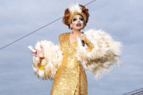 Biance Del Rio in a gold sequinned wrap dress and fur shrug, on the cusp of telling a joke