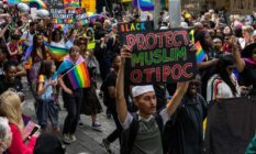 Man holding a 'protect Muslim QTIPOC' placard in a Pride parade