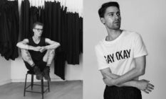 Designer Lauri Järvine sitting in front of a rail of black clothes and a model wearing a white t-shirt reading Gay Okay