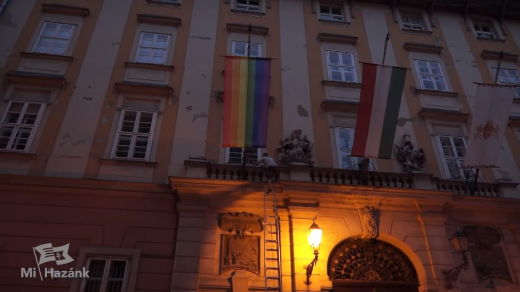 A far-right Hungarian politician has been arrested after using a ladder to climb the front of Budapest City Hall to pull down a Pride flag.