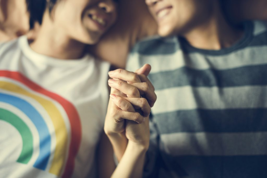 Lesbian couple holding hands, one wearing a rainbow t-shirt and another in a green striped top