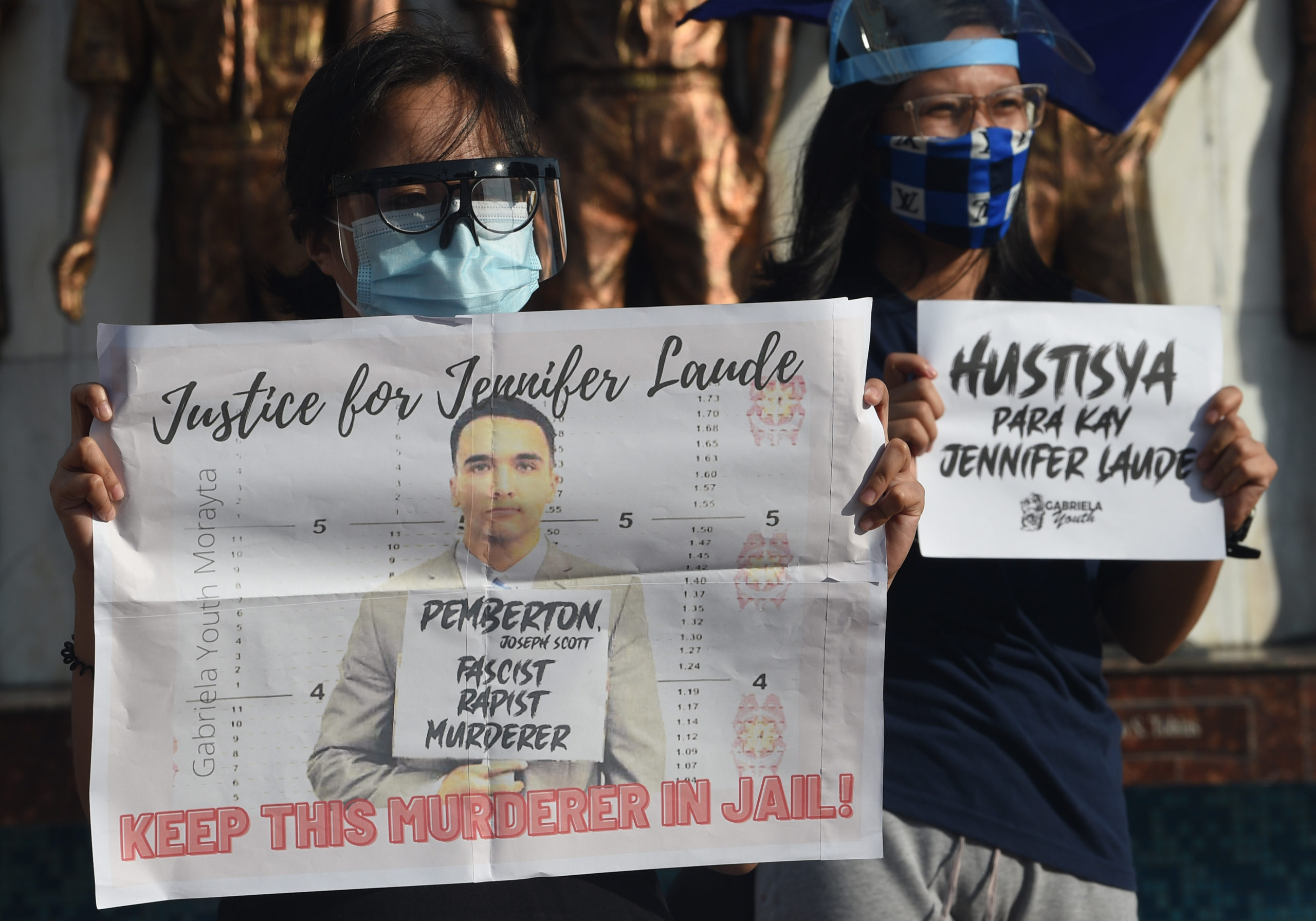Demonstrators in Manila display placards to protest against Philippine President Rodrigo Duterte's decision to pardon US marine Lance corporal Joseph Scott Pemberton who was convicted of killing Jennifer Laude
