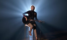 Taylor Swift sitting on a stool, playing acoustic guitar, with a spotlight behind her putting her into partial silhouette