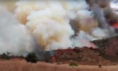 Hills covered in smoke from a wildfire stretching 7,000 acres
