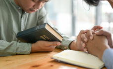 Two people praying with a bible
