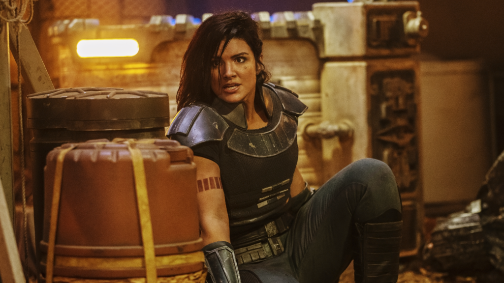 Gina Carano as Cara Dune in The Mandalorian in a body-armour style outfit, hiding behind a barrell
