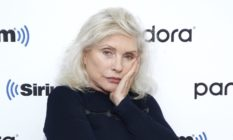 Debbie Harry in a black jumper with silver hair, resting her face on her hand