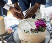 Close-up of two male hands cutting a wedding cake