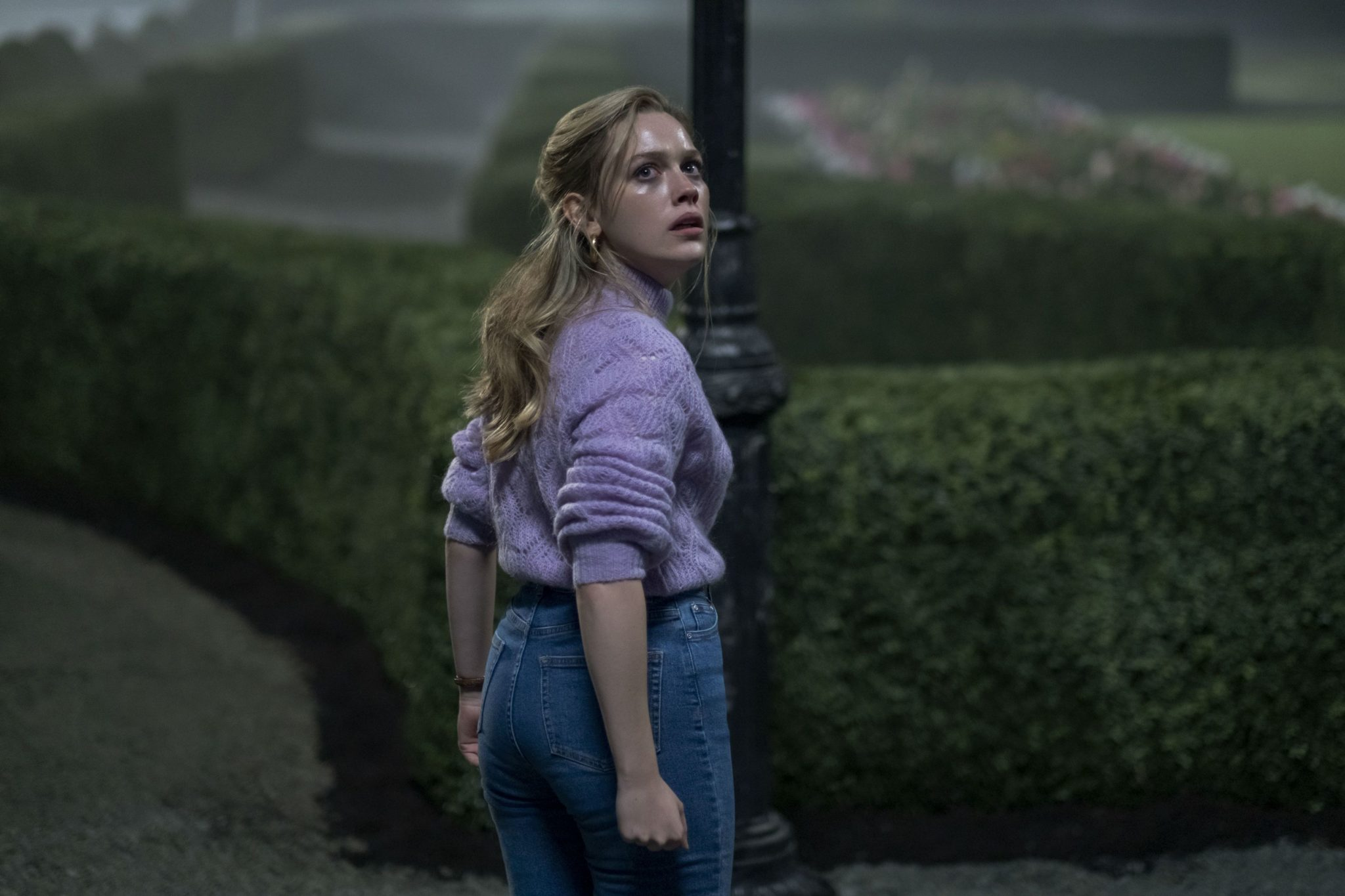 Dani standing in front of some bushes in the Haunting of Bly Manor