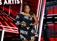 Lizzo in a black dress with the word VOTE in bold white text all over