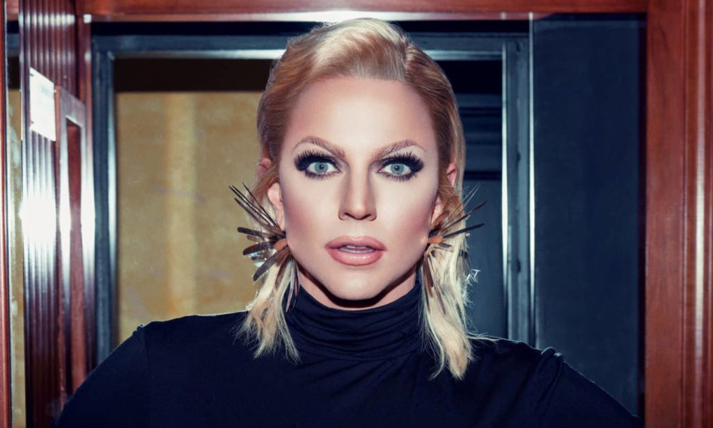 Courtney Act with shoulder-length blonde hair, tucked behind her ears, and big spiky earrings
