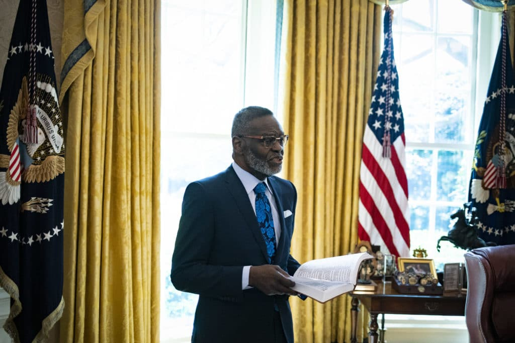 Bishop Harry Jackson, senior pastor at Hope Christian Church in Beltsville, Maryland, offers a blessing to President Donald Trump in the Oval Office of the White House on April 10, 2020